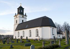 Bild på en vit kyrka med omgivande kyrkogård.